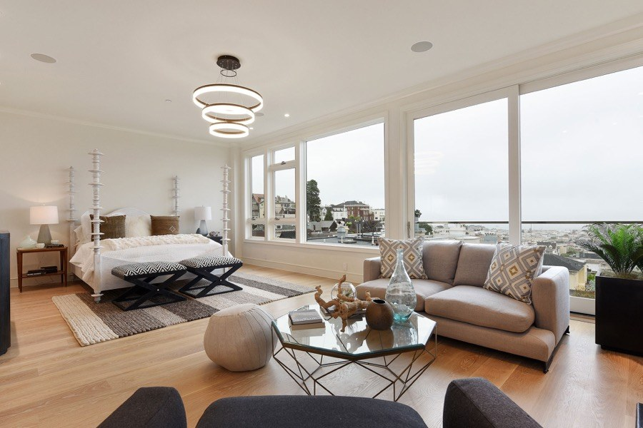 Broadway Modern Master Bedroom With Oversized Windows, Coffee Table, Chair, Couch And Modern Lighting Fixture