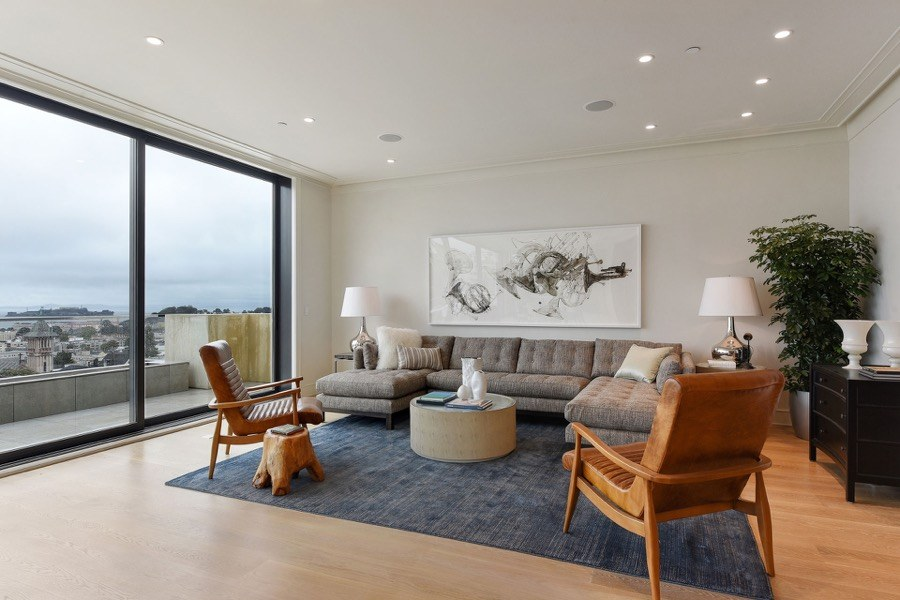 Broadway Open Seating Area With Floor To Ceiling Windows, Large Couch, Chairs And Circular Coffee Table
